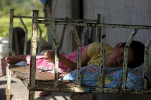 HIV patient Ma Sreymom, 15, rests in front of her home at Tuol Sambo village on the outskirts of Phnom Penh December 1, 2015. World AIDS Day falls on December 1. REUTERS/Samrang Pring - RTX1WLJ7