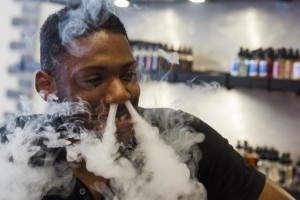 A sales clerk exhales vapor while smoking with a vaporizer during a wait for customers at the e-cigarette shop Henley Vaporium in New York, June 23, 2015. REUTERS/Lucas Jackson  - RTX1HS5K
