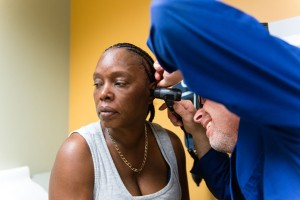 Tracy Young, 50, gets her ears checked by Brian Schlesinger, a physician's assistant, during her physical exam at the San Fernando Mental Health Center in Granada Hills, Calif., on Monday, February 8, 2016. (Heidi de Marco/KHN)