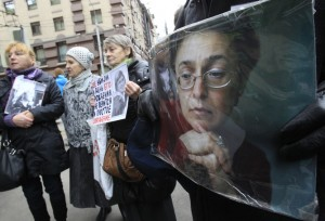 People hold portraits of slain journalist Anna Politkovskaya on the sixth anniversary of her death, next to her block of flats in central Moscow October 7, 2012. REUTERS/Sergei Karpukhin (RUSSIA - Tags: POLITICS CRIME LAW ANNIVERSARY MEDIA) - RTR38VU2