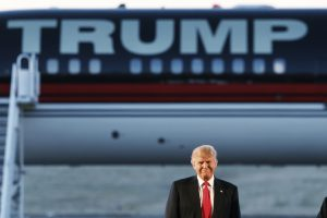 Republican U.S. presidential candidate Donald Trump stands in front of his plane  during a campaign rally at the airport in Millington, Tennessee