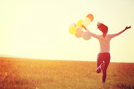 Young Asian woman running in a field holding balloons
