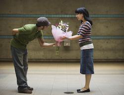 Man handing woman flowers